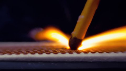 The match moves on the side of the matchbox and light the fire. Closeup. Shallow depth of field. Slow motion. Color correction