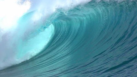 SLOW MOTION CLOSE UP: Big powerful Teahupoo tube wave breaking and splashing over the island reef, water drops spraying in the wind in sunny summer