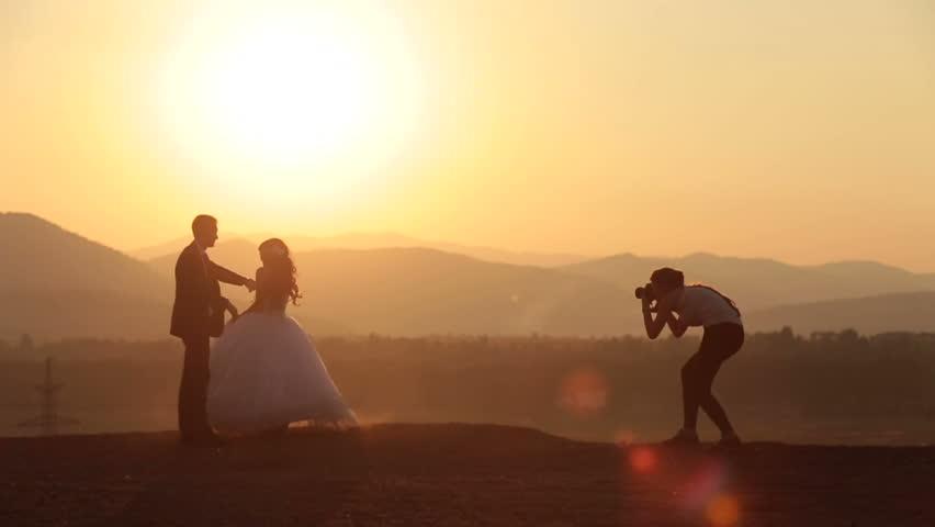 Woman-photographer takes photos of wedding couple in the Alpine mountains