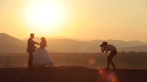 Woman-photographer takes photos of wedding couple in the Alpine mountains