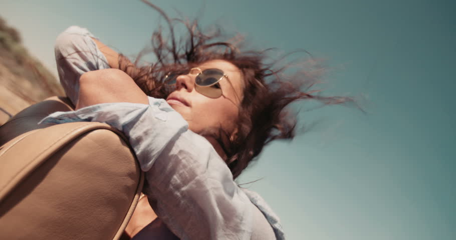 Boho girl relaxing and enjoying a road trip on the back seat of a convertible car with hair moved by the wind on a sunny day