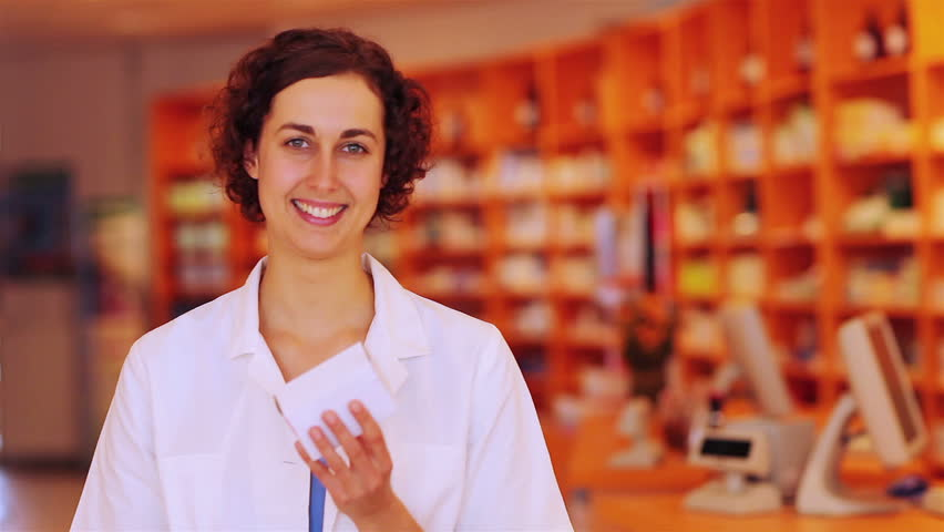 Happy pharmacist in pharmacy holding her thumb up
