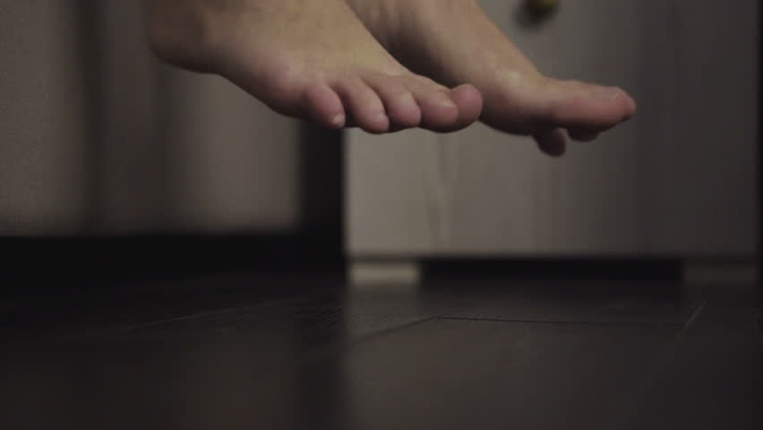 Close-up footage of feet getting out of bed.
