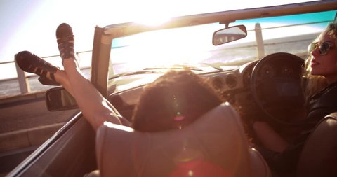 Two young women enjoying a summer sunset on seaside sitting in a vintage convertible with sunflare