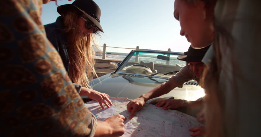 Teenager friends planning their beach road trip looking at a map leaning to the bonnet of a convertible on a summer sunny day