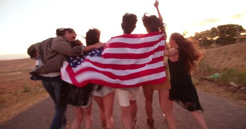 Group of multi-ethnic hipster friends have a walk on the country road hugging each other and holding an American flag