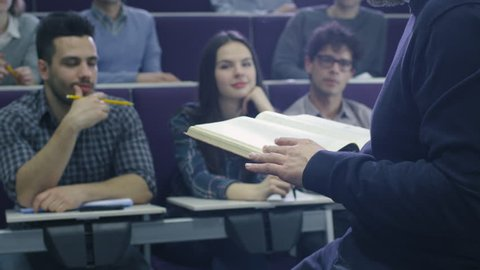 College professor is teaching a class of multi-ethnic students while holding a book. Shot on RED Cinema Camera in 4K (UHD).