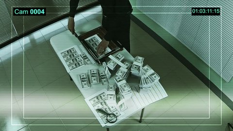 Criminal man in a clandestine laboratory cuts counterfeit money. CCTV record.