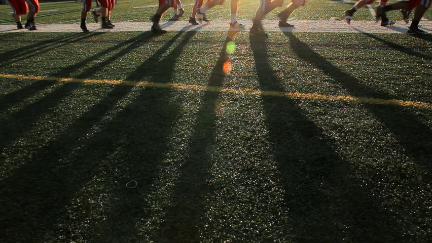 Players running past the frame with focus on their shadows during sundown.