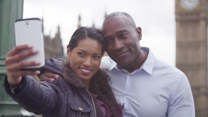 4k Attractive couple taking a selfie on smartphone in front of London's big ben | Shutterstock HD Video #15194713