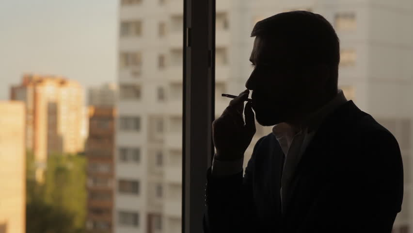 Young man smokes a cigarette at the window #15217603
