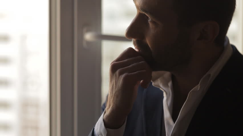 Thoughtful man standing at the window | Shutterstock HD Video #15217813