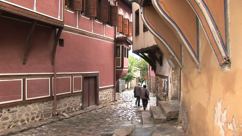 two people walking down an old street of plovdiv