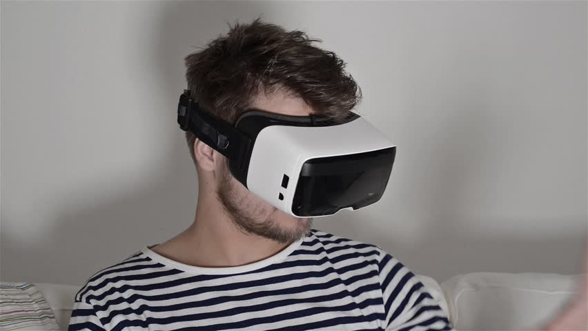 Man wearing virtual reality goggles. Studio shot, white couch   Shutterstock HD Video #15240394