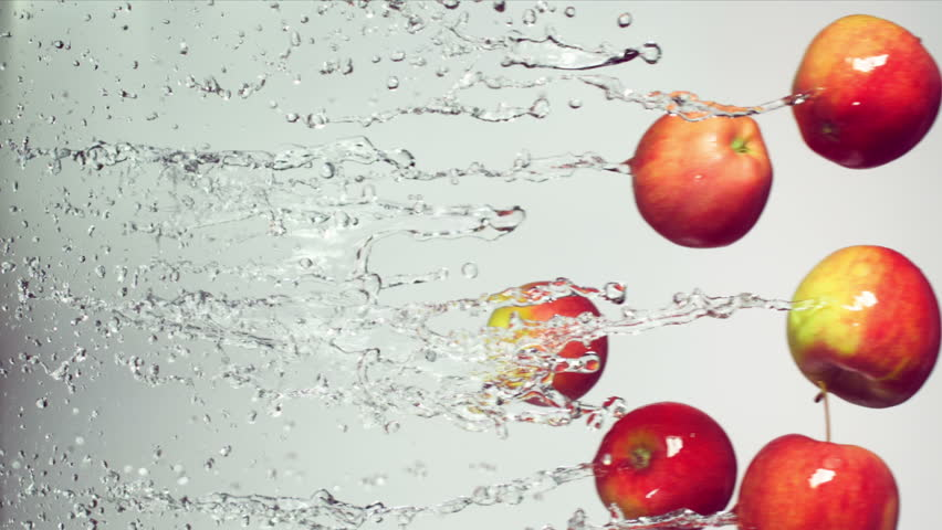 Red apple with splashes of water on a white background, slow motion