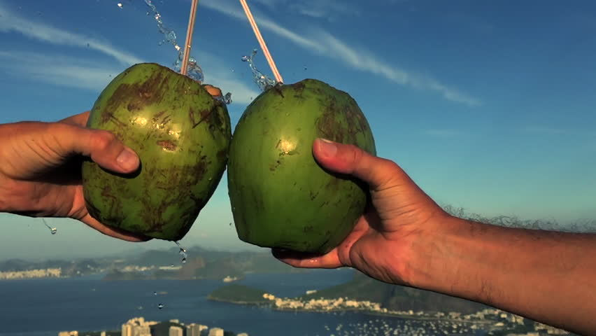 Hands holding fresh green drinking coconuts come together in a cheers toast above the Rio de Janeiro Brazil skyline