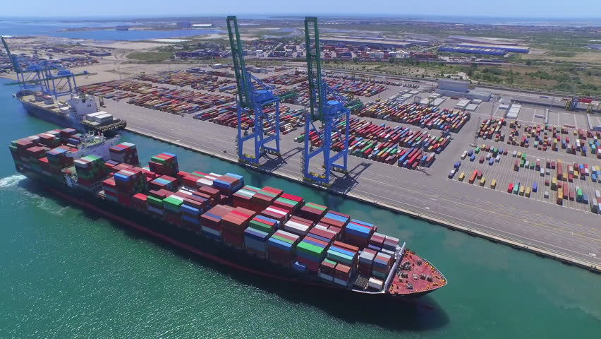 AERIAL: Fully loaded container ship docked at freight port terminal
