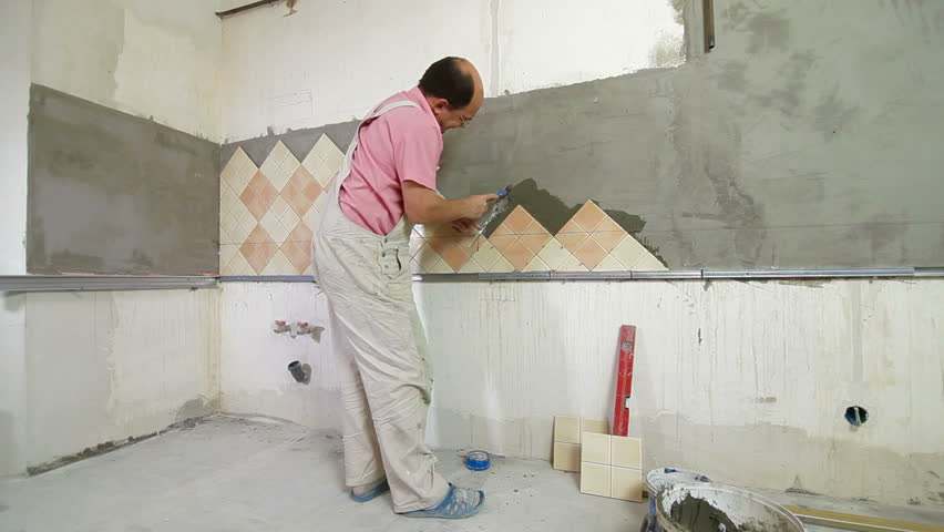 Worker Installing Tiles To A Kitchen Wall, Rear View, Wide Angle ...