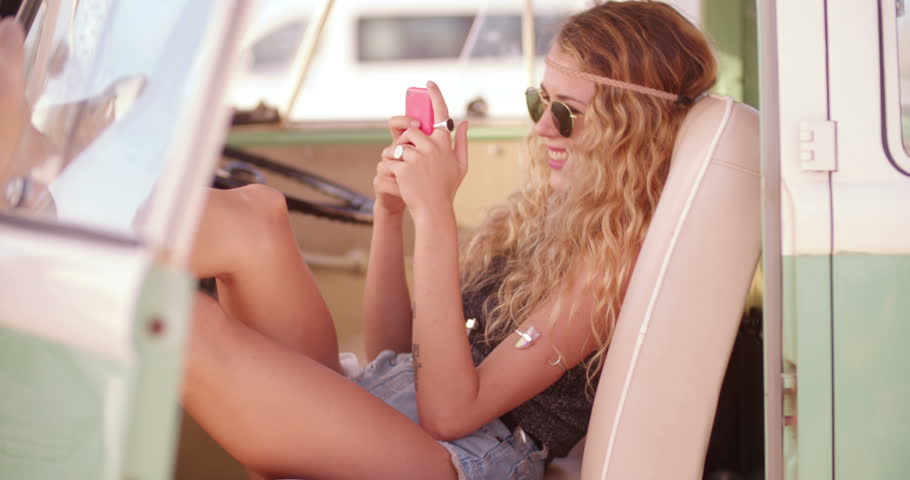 Road Trip Blonde boho girl rests her legs on the open door of a parked retro van at beach while looking at her phone and smiling