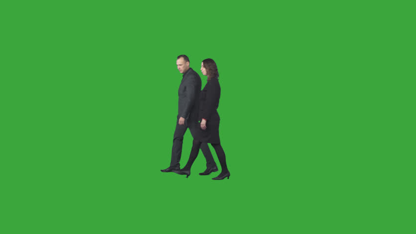 Two business colleagues in black and grey office clothes walk & discuss about corporate matter. Green screen footage. File format - .mov, codec PNG+Alpha. Shutter angle -180 (native motion blur)