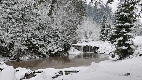 It is snowing over winter waterfall - 4K