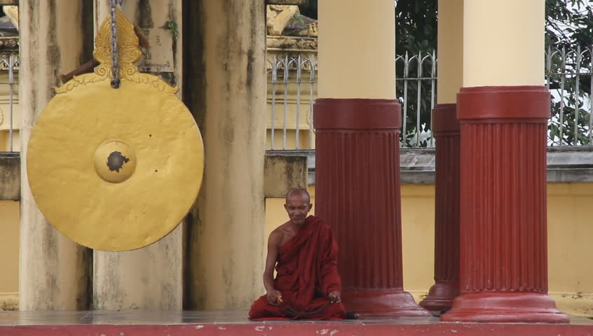 YANGON, MYANMAR - AUGUST 18: Buddhist monk prays near shrine in buddhist temple Ne Vin on August 18, 2011 in Yangon, Myanmar. Buddhist monks, who are venerated throughout Burmese society