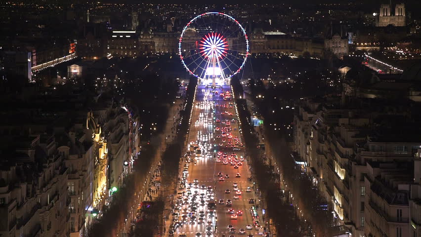 Aerial night view of the famos ferris wheel of the Place de la Concorde in Paris as seen from the top of the Arc de Triomphe along the Champs Elysees boulevard. Vertical pan going up on the street.