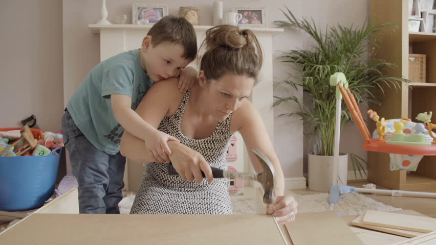 Mother Teaching Her Son How To Nail Using A Hammer With Flat Pack DIY Kit