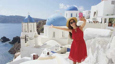 Woman taking phone selfie On travel in Oia, Santorini using smartphone by blue domed church. Female tourist sightseeing enjoying summer vacation visiting landmark destination in Greece, Europe