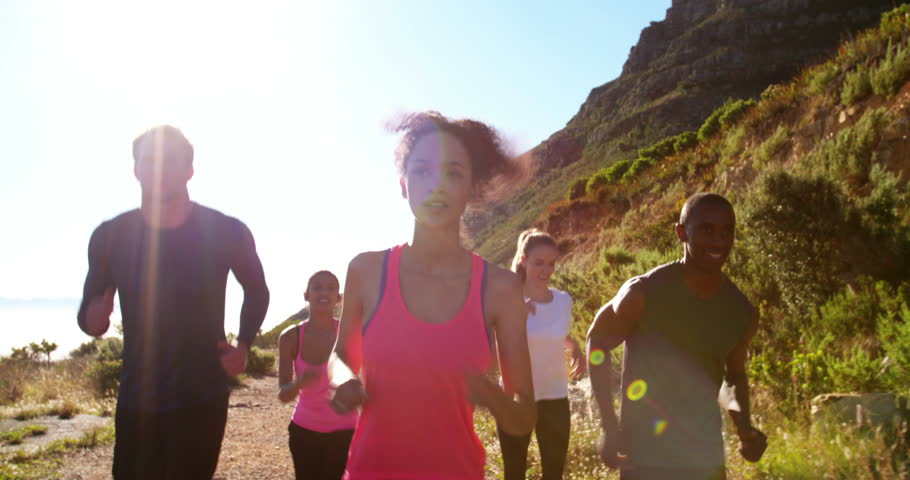 Group of multi-ethnic friends doing a running training outdoors on a footpath