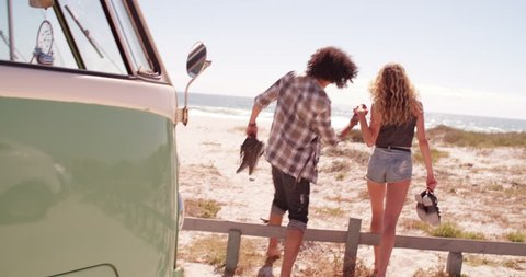 Mixed race hipster man and caucasian hipster woman hold hands and walk bafrefoot together towards a sandy beach from parked retro van, the couple on a road trip