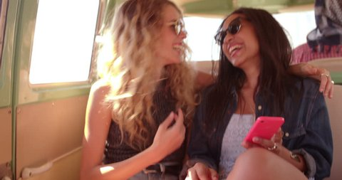 Boho or hipster fashion woman laughing out loud looking at her smart phone with mixed race girl friend in vintage van during a road trip.