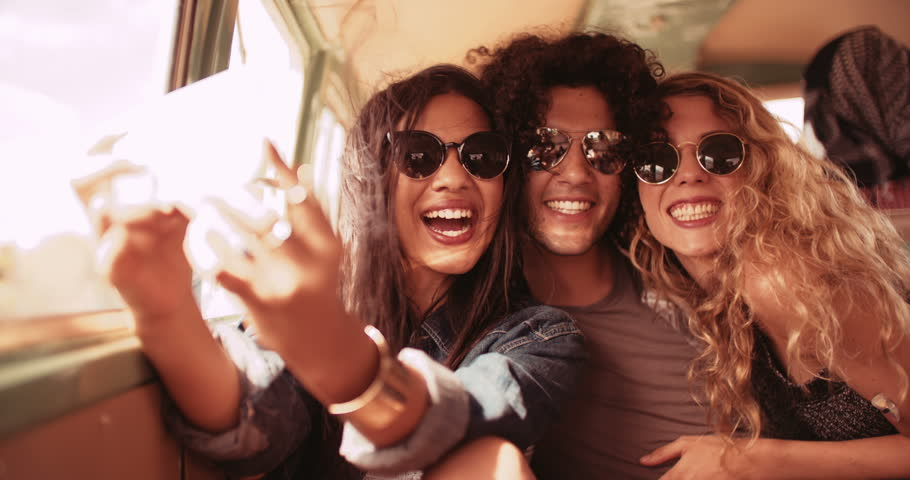 Road trip friends in a car. Mixed race man and woman and caucasian woman taking a selfie in back of a retro van | Shutterstock HD Video #15333256