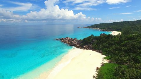 Aerial view (landscape) of tropical paradise beach (coast) with white sand and azure sea water (Indian Ocean), sunny summer day, Grand Anse, La Digue Island, Seychelles islands vacation, UHD 4K