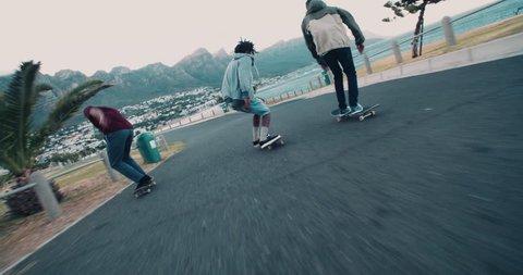 Multi-Ethnic group of skater friends skating down street along seaside