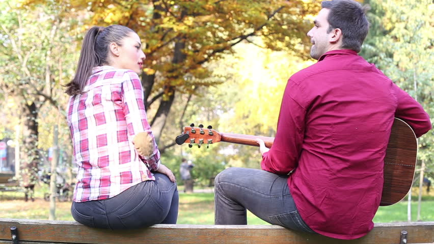 Back view of handsome man playing guitar while beautiful young woman singing, sitting next to him on bench in park | Shutterstock HD Video #15381133