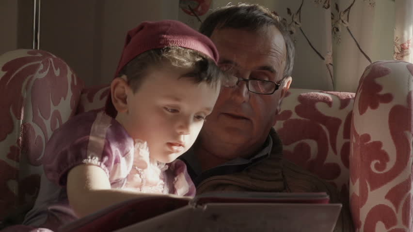 A grandfather is reading a story book to his grandson. The grandson is dressed up as a princess from the story in the gender blender style. Shot in a modern British house.