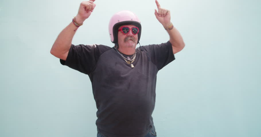 Silly senior adult man with pink safety helmet and red heart shape sunglasses dancing , isolated on blue wall background