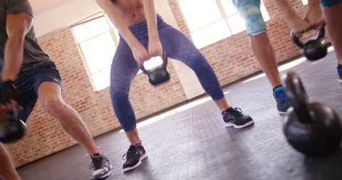 Multi-ethnic group of young adult athletes doing kettlebell exercise during a crossfit workout at the gym