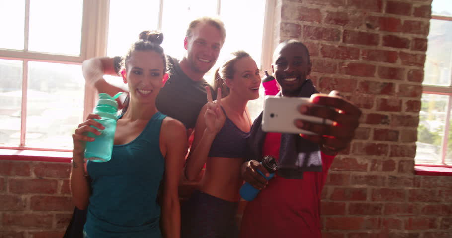 Multi-ethnic group of young adult friends grimacing and smiling to take a self portrait with a smartphone at the gym