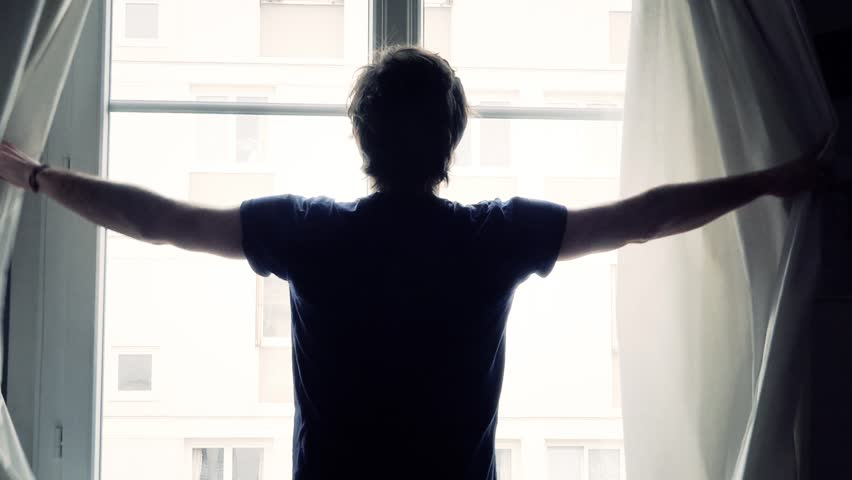 Backlit Man Opens Curtains And Stretches - 60fps. Silhouette of a man opening the curtains in the morning on a sunny day. | Shutterstock HD Video #15392953