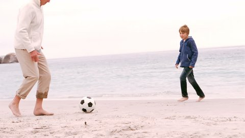 Family playing football at the sea