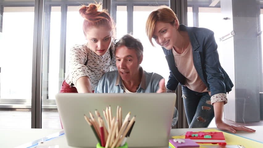 Middle age creative director looking at laptop with his team and discussing plans   Shutterstock HD Video #15414007