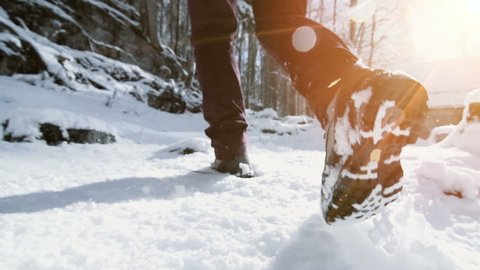 slow motion close up of feet walking in snow landscape. winter hiking journey adventure background
