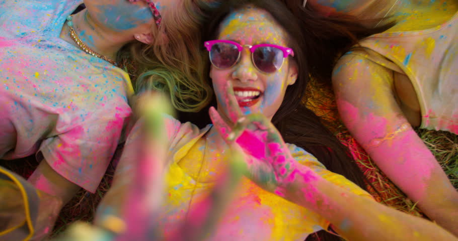 Multi-Ethnic group covered in Holi powder lay in grass laughing and looking up and gesturing peace sign to the camera in a park at a Holi festival in the summer | Shutterstock Video #15427240
