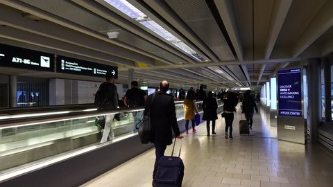 ZURICH - FEBRUARY 29, 2016: Transfer passengers run at passage, POV camera walk forward. Airport passageway, unidentified man with roll-aboard bag quickly pace, people hurry to connecting flight