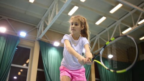 Under view of girl learning to beat off balls during tennis training