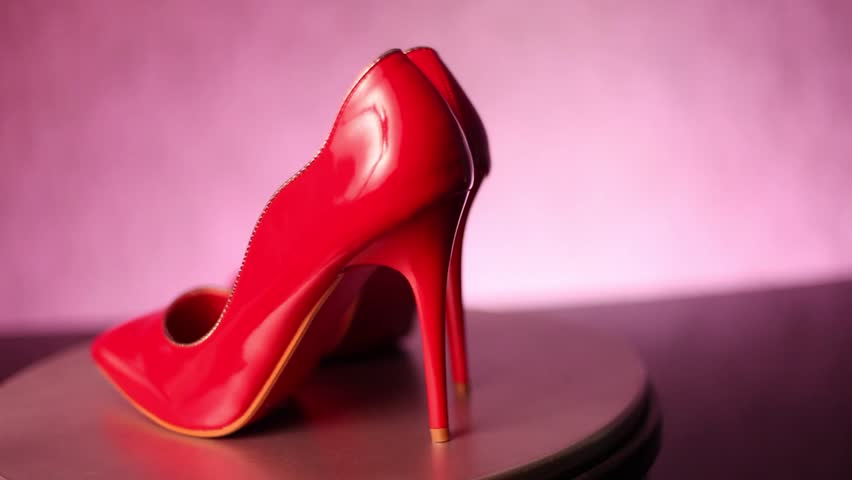 Rotating red, glossy stiletto high heel shoes on shop display doing 180 degrees in a tilted frame