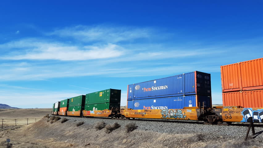 Train cars with multicolored containers passing by in the desert with a locomotive pushing the string. | Shutterstock HD Video #15445786