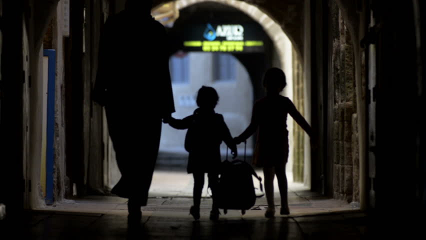 Dark old street of Essaouira in Morocco and mother with children reaching the camera #15454333